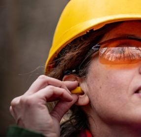 Woman in hard-hat and goggles putting in ear plug