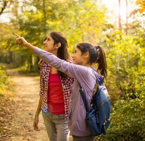 Two girls with hearing aids in woods during autumn