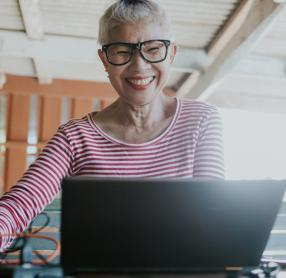 Elderly woman smiling while on her laptop
