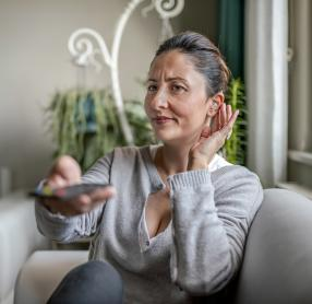 Middle-aged woman with hearing aid struggling to hear television