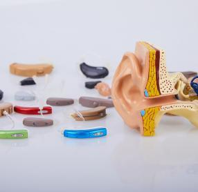 Table covered with hearing aids beside medical model of ear